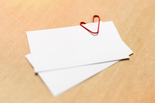 공예 종이 바탕에 빈 흰색 명함입니다. 심장 모양에 빨간 종이 클립. 확대