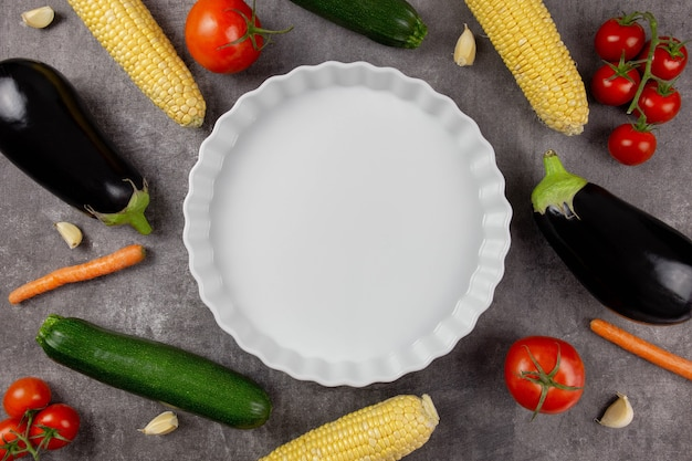 Empty white ceramic baking dish on a dark background with autumn vegetables. food cooking background in an oven for your text.