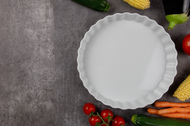 Empty white ceramic baking dish on a dark surface with autumn vegetables