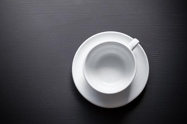 Empty white ceramic coffee mug over black background