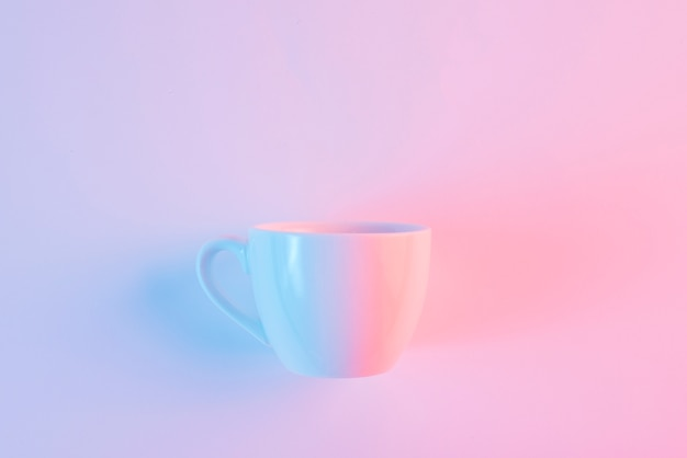An empty white ceramic cup against pink backdrop