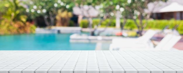 여름 배너 배경의 열대 리조트에 있는 빈 흰색 세라믹 모자이크 테이블 상단과 흐릿한 수영장 - 제품을 전시하거나 몽타주하는 데 사용할 수 있습니다.