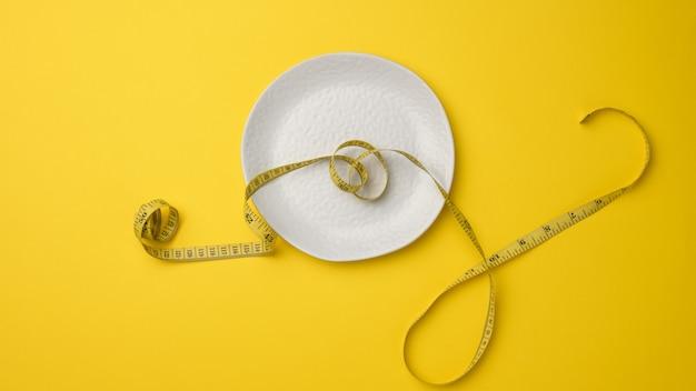 空の白いセラミックプレートと黄色の背景に巻尺。健康的な栄養の概念、減量