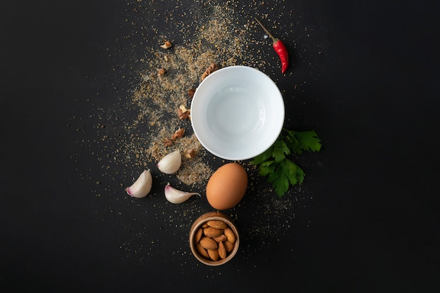 Empty white ceramic plate on the black table, fresh ingredients for cooking, ground pepper, tableware