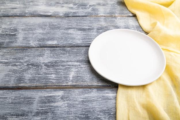 灰色の木製の背景と黄色のリネンの織物に空の白いセラミックプレート。側面図、