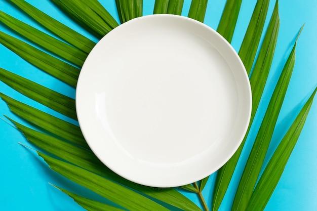 Опорожните белую керамическую плиту на тропической ладони выходит на голубую предпосылку.