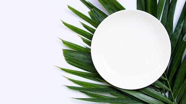 Пустая белая керамическая тарелка на тропических пальмовых листьях на белом фоне. вид сверху