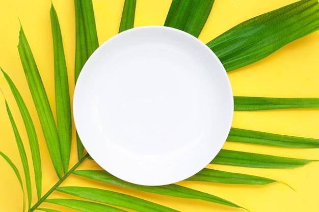 Пустая белая керамическая тарелка на тропических пальмовых листьях на желтом фоне.