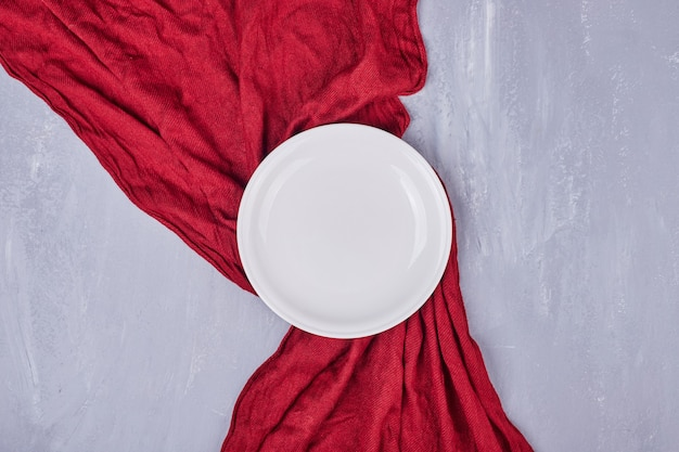An empty white ceramic plate on the tablecloth.