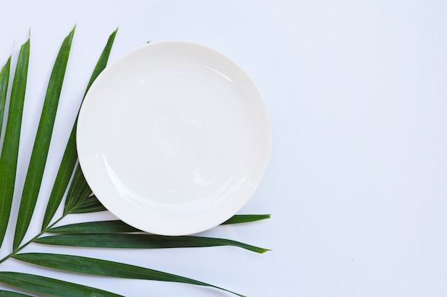 Empty white ceramic plate on tropical palm leaves on white background. top view