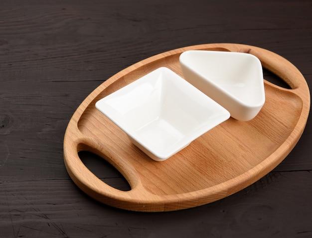 Пустые белые керамические тарелки и овальный деревянный поднос на деревянном фоне, вид сверху