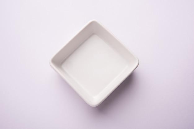 白または灰色の表面上に分離された空の白いセラミックサービングボウル