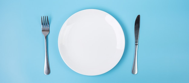 青の背景にナイフとフォークで空の白いセラミックプレート。ダイニングとキッチン用品のコンセプト