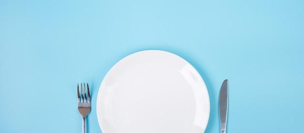 파란색 배경에 나이프와 포크가 있는 빈 흰색 도자기 접시. 식사 및 주방 용품 개념