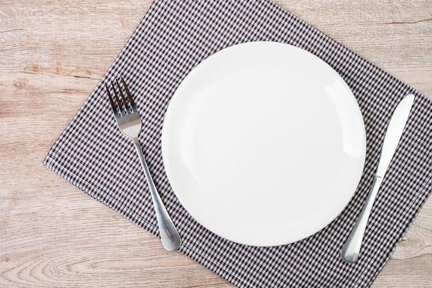 テーブルの背景にナイフとフォークで空の白いセラミックプレート。ダイニングとキッチン用品のコンセプト