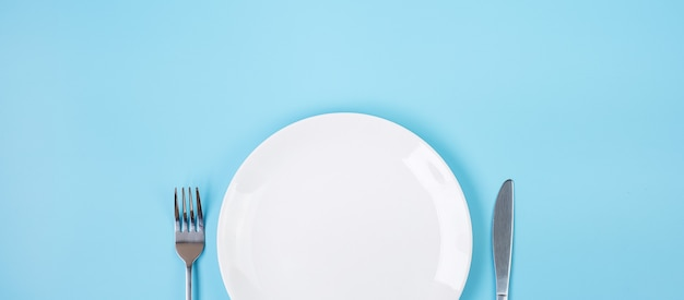 Empty white ceramics plate with knife and fork on blue background. dining and kitchenware concept