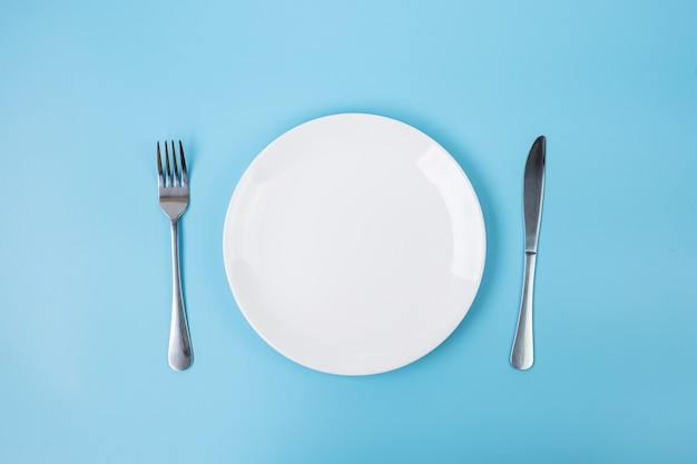 Empty white ceramics plate with knife and fork on blue background