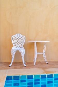 빈 흰색 의자와 테이블 옆에 수영장