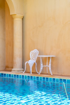 Empty white chair and table on side the swimming pool