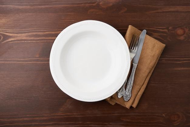 Пустой белый круг керамическая тарелка на деревянном фоне с серебряными изделиями и льняной салфеткой