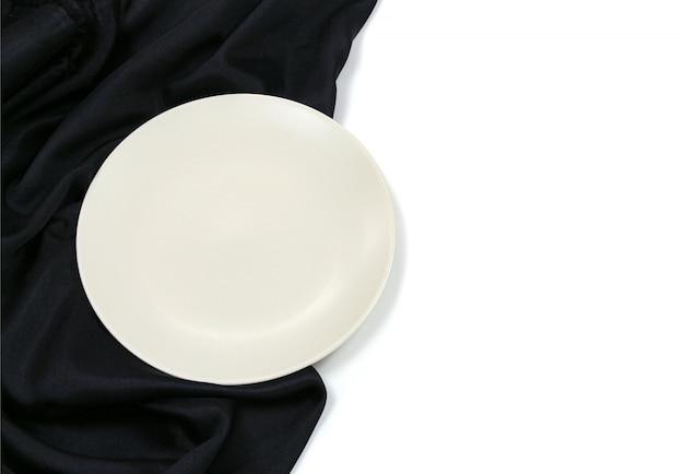 Пустой белый кружок современная керамическая тарелка с шелковой скатертью текстуры на белом фоне