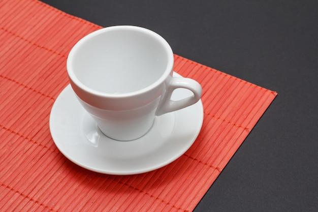 黒の背景を持つ赤い竹ナプキンに空の白いコーヒーカップとソーサー。上面図。
