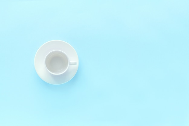 Empty white coffee cup and dish saucer on blue background