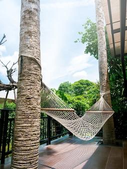 空の白い綿のロープクレードル。屋外庭園近くの木製テラスで、2本のヤシの木の間にぶら下がっているスイングハンモック、垂直スタイル。