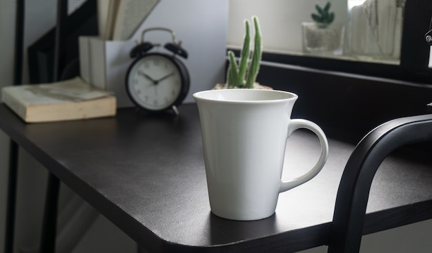 Empty white cup on bedside table in hotel bedroom