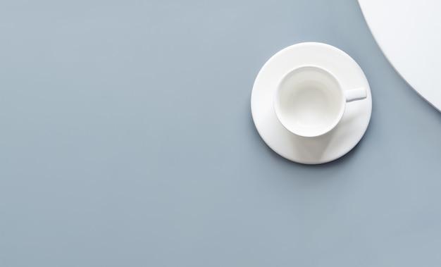 회색 배경에 빈 흰색 컵입니다. 평평한 바닥, 평면도, 오버 헤드. 마실 것을 모의하십시오. 미니멀리즘.