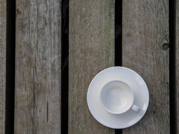 Empty white cup on wooden tabletop. copy space.
