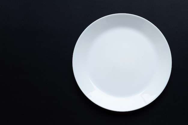 暗い表面に空の白い皿皿。上面図