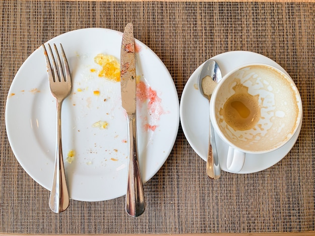 Empty white dishes and coffee cup with after breakfast on wooden table.