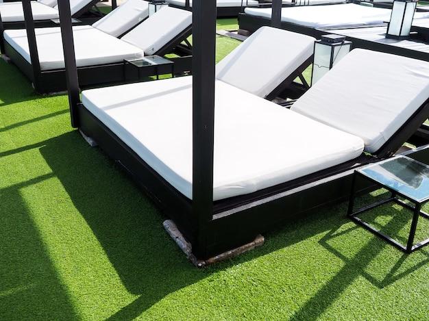 夏の晴れた日に緑の人工芝に空の白いダブルサンベッド。