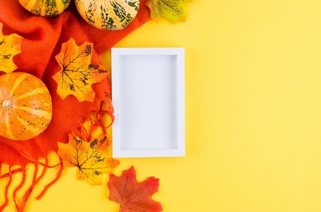 Empty white frame, decorative mini  pumpkins, fall dried leaves and sharf