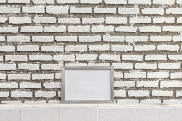 Empty white frame on the grunge brick wall, mock up to display or montage of your content.