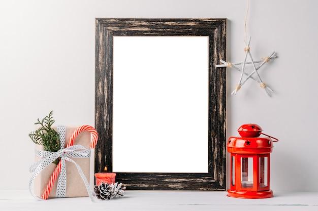 空の白いフレームのモックアップ。白のクリスマスの装飾と黒の木製フレーム