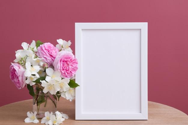 空の白いフレームはピンクの背景に花でモックアップします。あなたのテキストや写真のためにtemlate