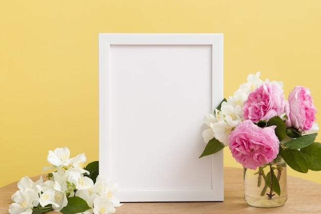 空の白いフレームは黄色の背景に花でモックアップします。あなたのテキストや写真のためにtemlate