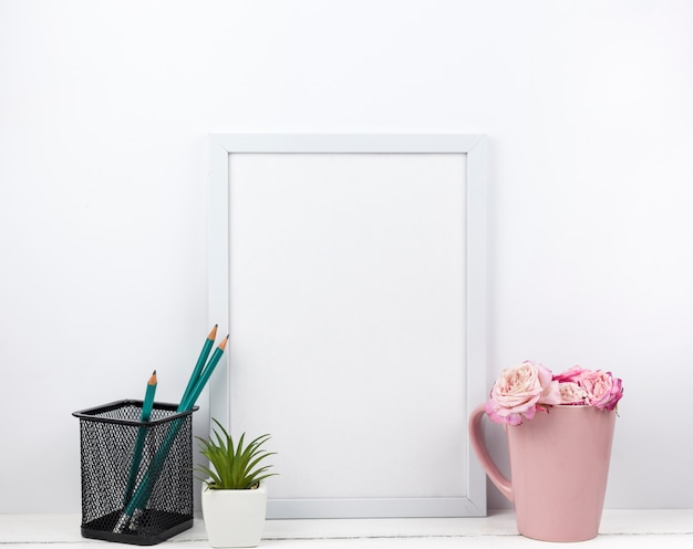 Empty white frame; pencil stand; flowers and succulent plant on table