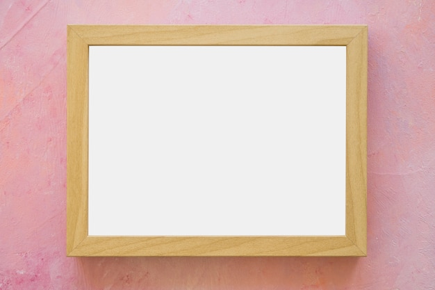 An empty white frame on pink painted wall