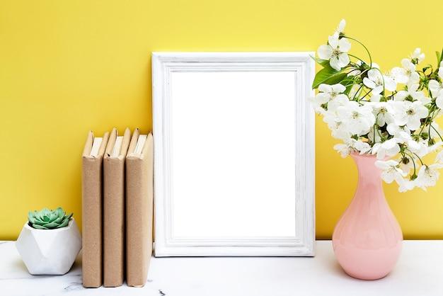 꽃병와 노란색 벽 근처 테이블에 책 빈 흰색 프레임. 당신의 텍스트를 봄.