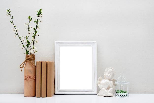 꽃병 및 테이블에 책 빈 흰색 프레임. 당신의 텍스트를 봄.