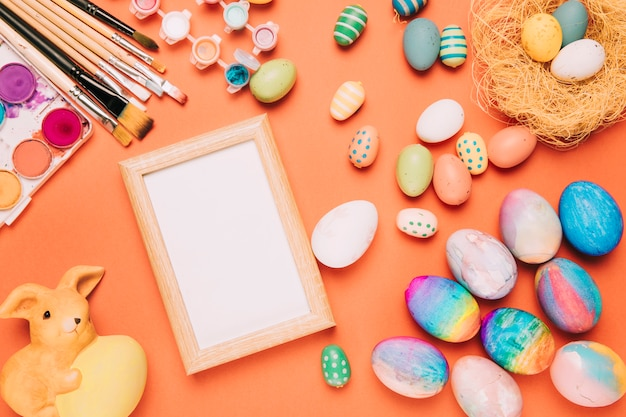 Empty white frame with colorful easter eggs; paint brushes; watercolor and rabbit statue on an orange background