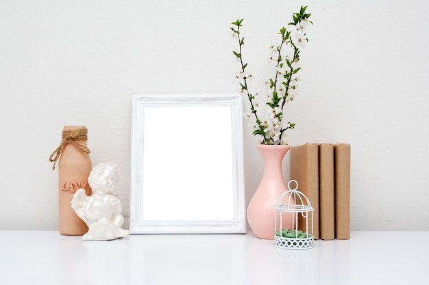 Empty white frame with a vase and books on the table. spring mock-up for your text.