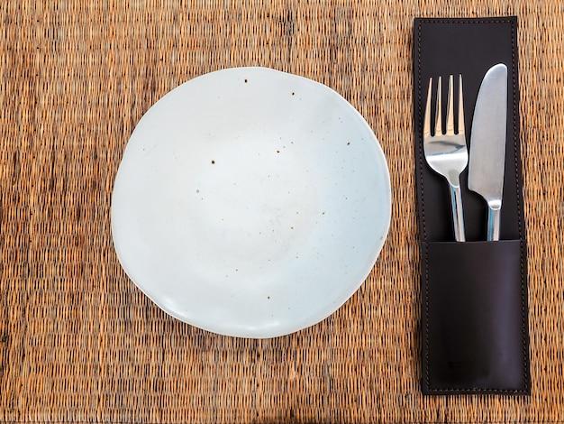 マットの上に革のケースにステンレスナイフとフォークが付いた空の白いフリーフォーム型の磁器皿