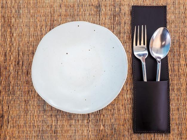 マットの上に革のケースにステンレススプーンとフォークが付いた空の白いフリーフォーム型の磁器皿