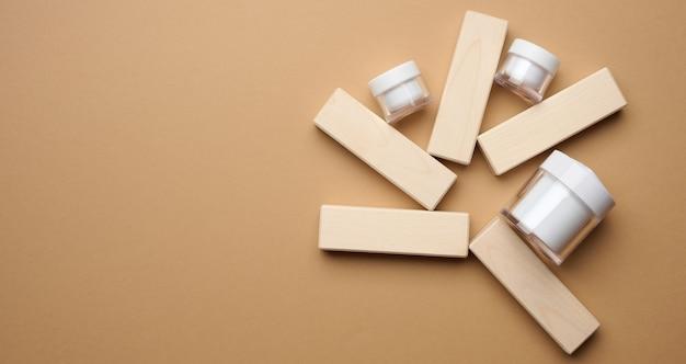 갈색 배경과 나무 블록에 화장품을 위한 빈 흰색 유리 항아리. 크림, 젤, 혈청, 광고 및 제품 판촉용 포장. 조롱, 평면도, 복사 공간