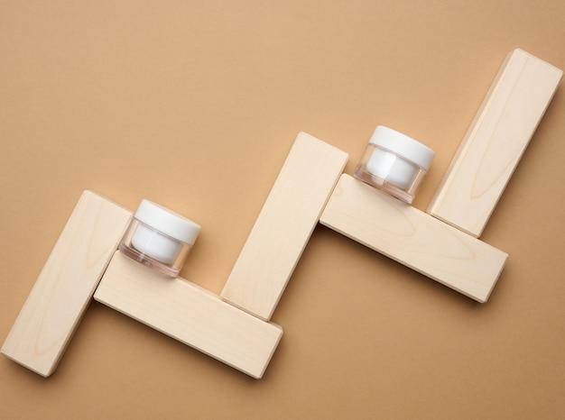 갈색 배경과 나무 블록에 화장품을 위한 빈 흰색 유리 항아리. 크림, 젤, 혈청, 광고 및 제품 판촉용 포장. 조롱, 평면도