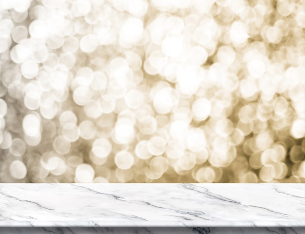 Empty white glossy marble table top with blur sparkling gold bokeh abstract background